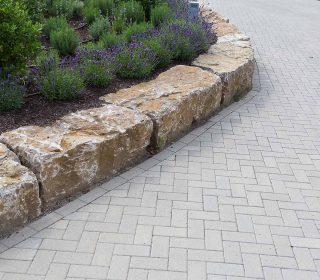 Pflastersteine und Natursteinmauer