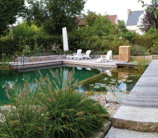 Eingefasster Schwimmteich mit Steg und Steinmauer