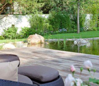Schwimmteich Wasserspiel und Holzliegefläche