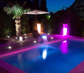 Beleuchteter Pool und Wasserschütten