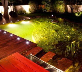Beleuchteter Schwimmteich und Strahler am Deck